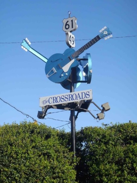 Crossroads with 3 blue guitar statues on a pole is a marker for Highways 61 and 49 in Mississippi