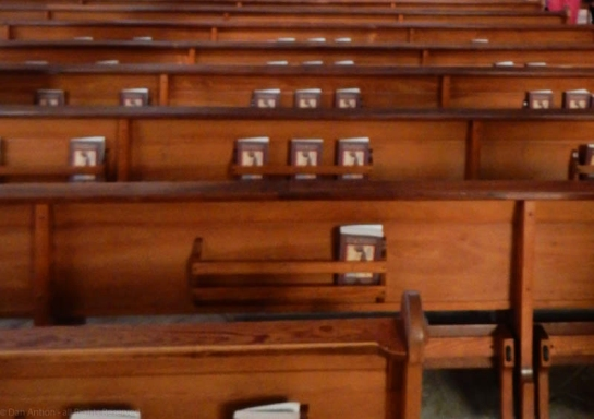 Church pews from back with hymnals, by Dan Antion