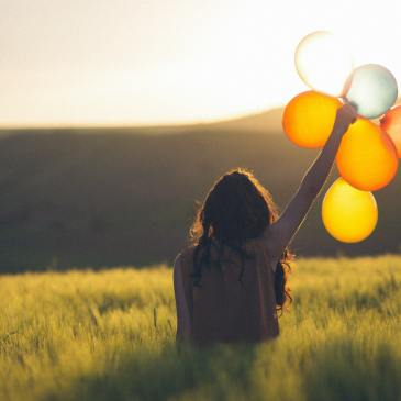 Girl holding up Balloons gold yellow Cata Unsplash