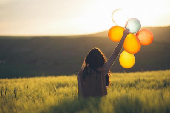 Girl holding up Balloons gold yellow Cata Unsplash